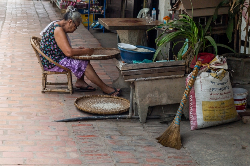 Elderly Lady Sifting Rice