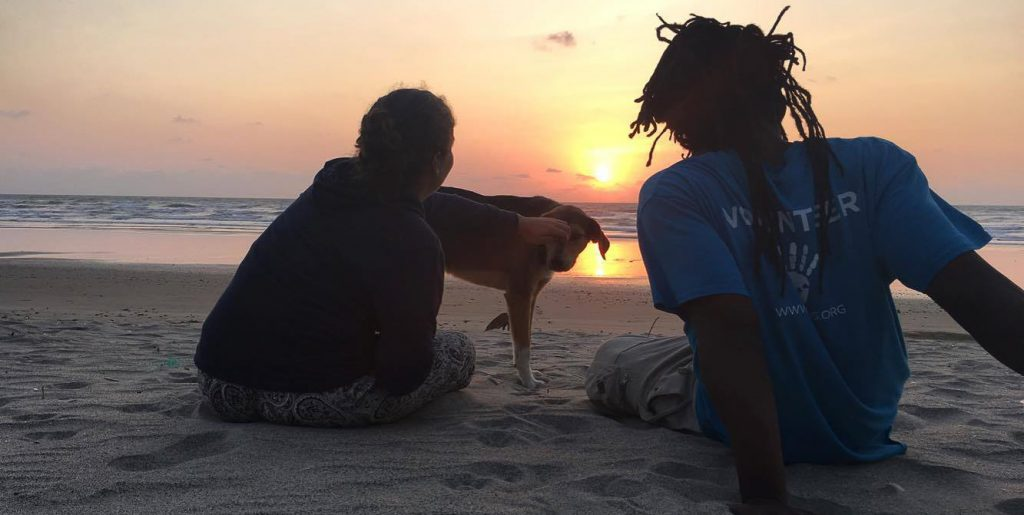 friends on the beach at sunset with dog