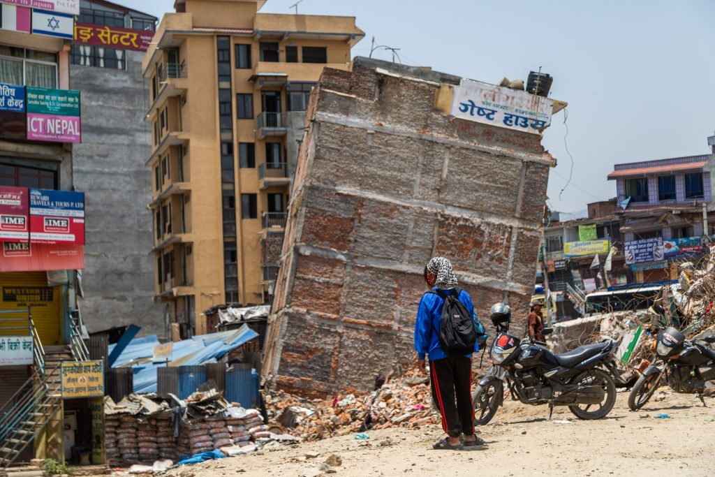 Man standing in front of  an earthquake damaged building.