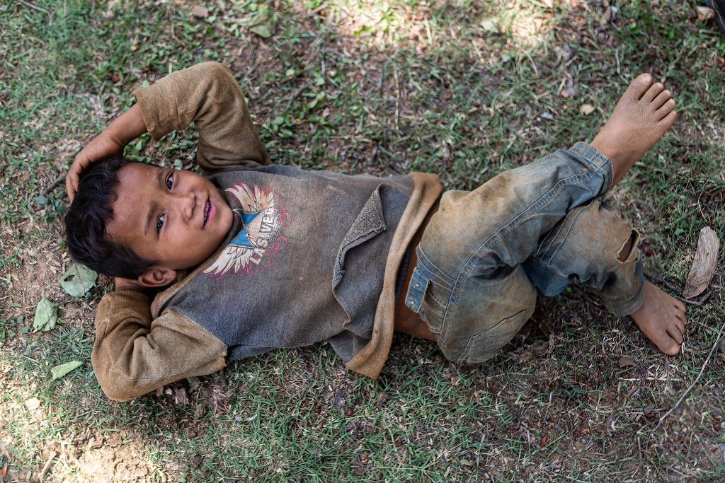 young boy lying down with his legs crossed